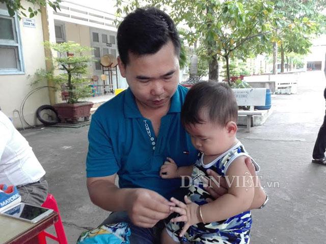 Chồng ẵm con nhỏ ngồi cổng trường đợi vợ thi THPT quốc gia - Hình 1
