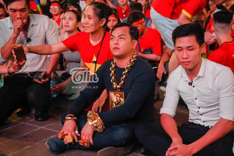 CĐV sáng nhất đêm nay: Đeo đầy vàng ra phố cổ vũ tuyển Việt Nam, 5 vệ sĩ đi theo bảo vệ - Hình 1