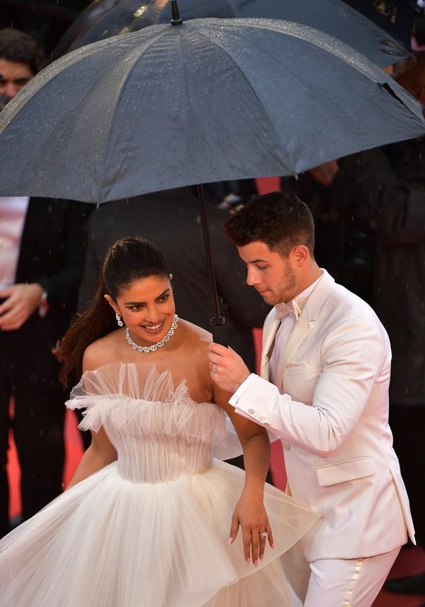 Chồng trẻ nâng váy, che ô cho Hoa hậu Thế giới trên thảm đỏ Cannes - Hình 4