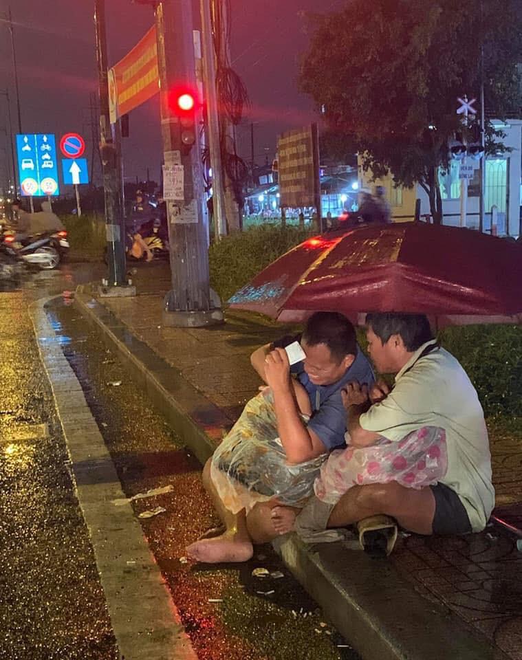 Xúc động cảnh 2 người đàn ông khiếm thị, nương nhau dưới cơn mưa đêm ở Sài Gòn để bán từng tấm vé số mưu sinh - Hình 1