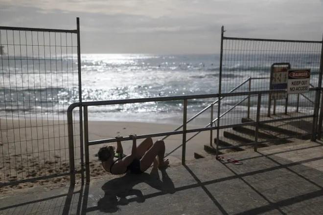 Bãi biển bị phong toả để chống dịch, dân Australia chui rào đi bơi - Hình 1